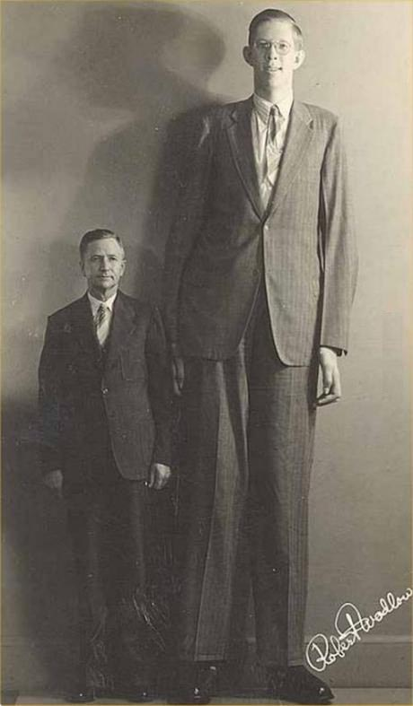 Robert Wadlow, the tallest man in recorded history, standing with his father of 5%2211