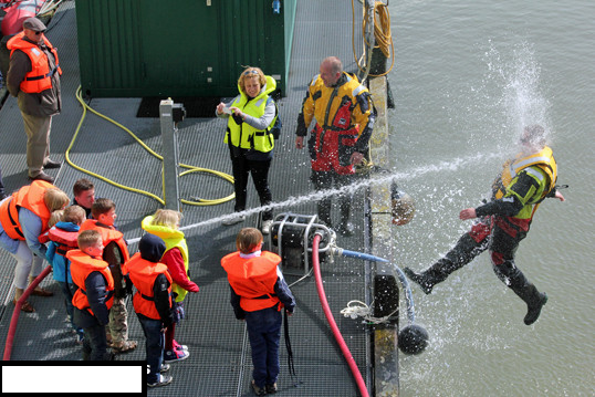 Kids playing with a water hose during coast guard demonstration.